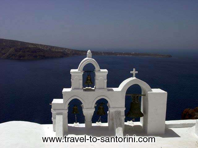 The view of Roka on Thirassia from behind a church in Oia. Genuine sample of the cycladic architecture we find on churches.