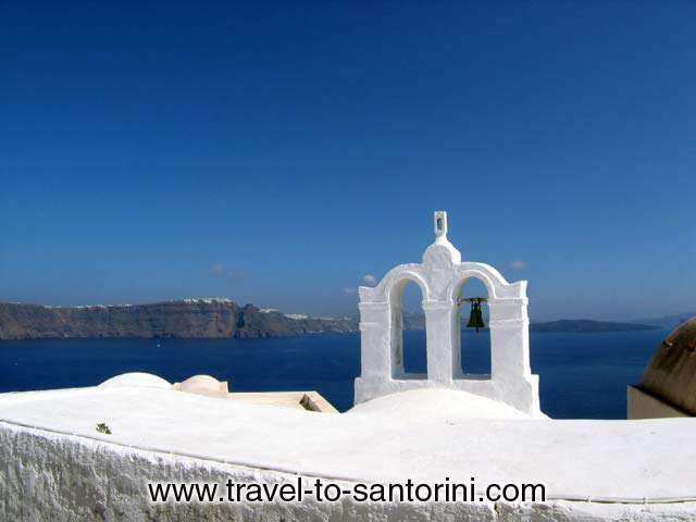 Church bell in Oia, Imerovigli and Kameni island (volcano) in the background.