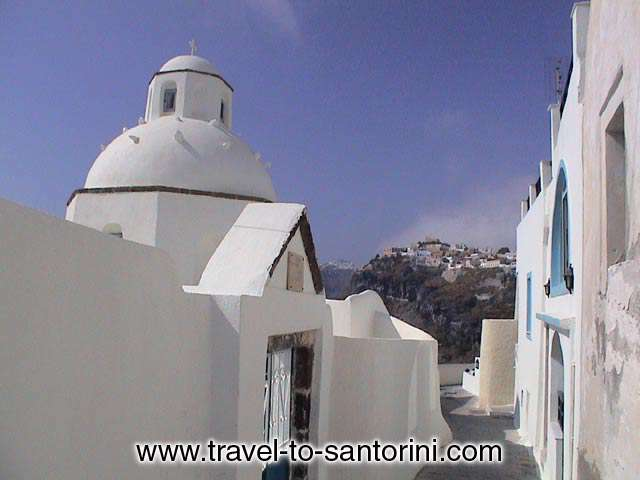 The church of Agios Minas in the narrow pathways at the edge of the Caldera. One of the most photographed churches in Santorini